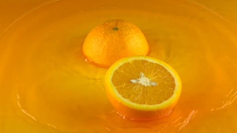 Orange hits orange juice surface and splits into halves. Slow motion video Live Action