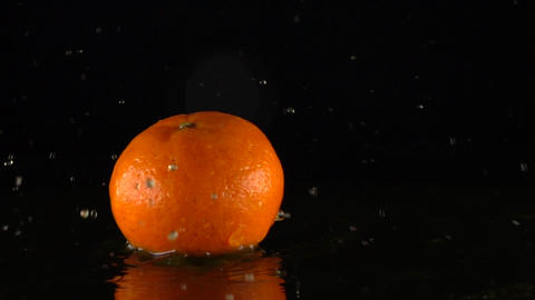 Falling mandarin hitting orange juice surface slow motion shot. Black background Footage