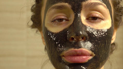 Beautiful young woman with cosmetic black face pack on her face. 4K close up Footage