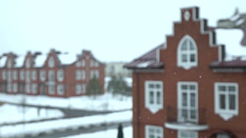 Super slow motion shot of snowflakes falling against blurred red brick townhouse Footage