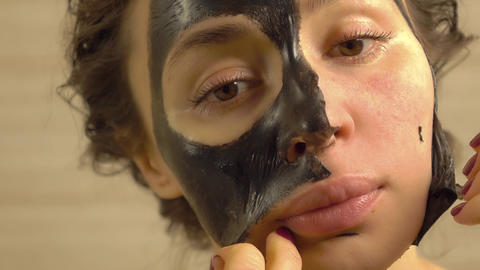 Beautiful woman removing elastic black face pack from her face Footage