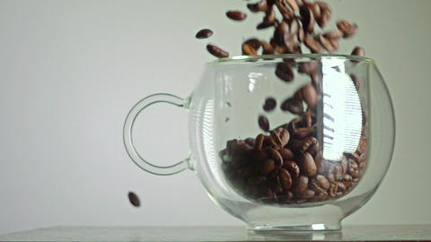 Roasted coffee beans being poured in a glass cup super slow motion video Footage
