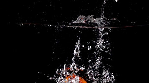 Super slow motion: four red tomatoes fall and float in water, black background Footage