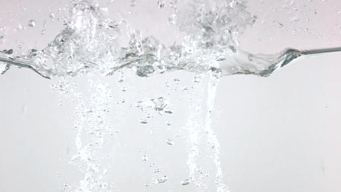 Several potatoes falling in water with white background. Super slow motion video Live Action