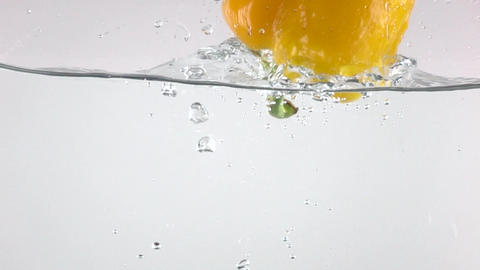 Super slow motion shot of yellow bell pepper falling down in water Footage