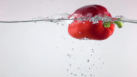 Red bell pepper falling down in water, light background super slow motion shot Footage