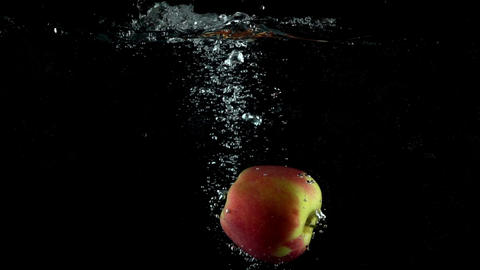 Red and green apple falling in water against black background. Super slow motion Footage