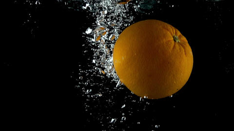 Single orange falling down in water against black background. Super slow motion Footage