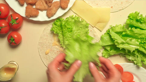 Girl cooking Caesar roll with flatbread, chicken, cheese, salad and tomatoes Footage