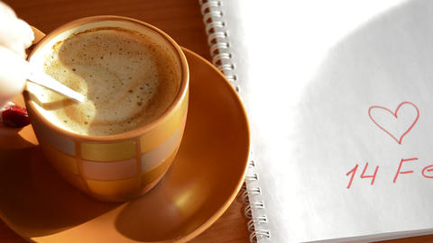 Woman's hand puts the coffee Cup near notebook with sign hearts February 14 Footage