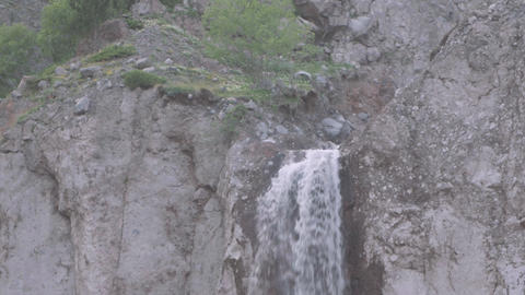 Waterfall flows down over rocky cliff in mountains Footage