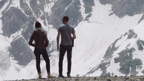 Young couple at mountain landscape see sight, snowy peaks Footage