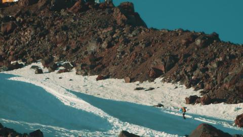 Man walks on mountain peak covered in snow using walking sticks Footage
