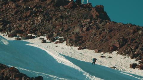 Hiker walks on mountain peak covered in snow using walking sticks Footage