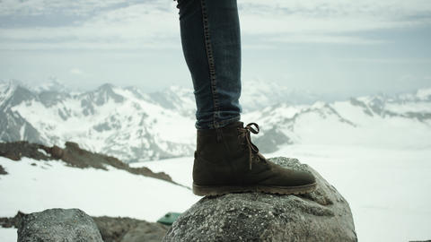 Hiker feet in leather shoe stomps on rock at snowy mountain scenic view Live Action