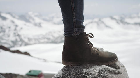 Hiker feet in leather shoe stomps on stone at snowy mountain scenic view Footage