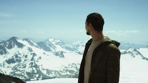 Young bearded man puts on sunglasses at snowy mountains with scenic view Footage