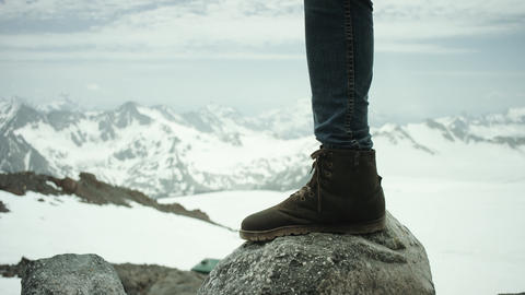 Hiker feet in leather boot stomps on rock at snowy mountain scenic view Live Action