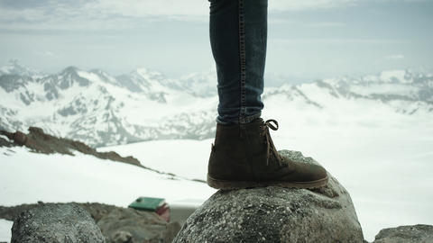 Adventurer feet in leather shoe stomps on rock at snowy mountain scenic view Live Action