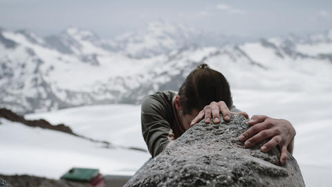 Young man traveler climbs rock at snowy mountain scenic view on sunny day Footage