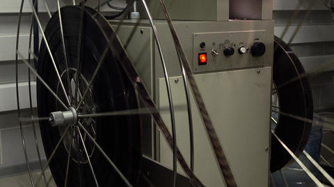Dolly shot of big rotating reels in pro cinema projector, 4K video, part of set Footage