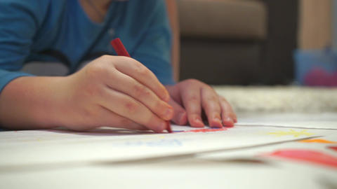 Woman and small boy drawing with color crayons in album Live Action