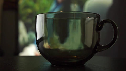 Pouring black tea in a glass cup against movie screen. Slow motion video Footage