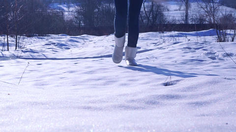 Girl in silver winter boots walking on sunny snow. Zoom out slow motion video Footage