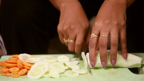 Closeup woman hand slicing cucumber. teenage girl cutting cucumber Footage