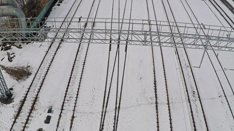 Multiple electrified railway tracks and switches in snow. Aerial view GIF