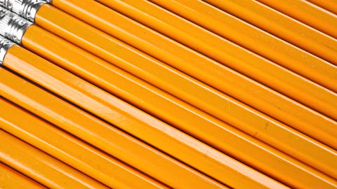 Row of identical sharpened pencils with orange coating. Equality concept, dolly Footage