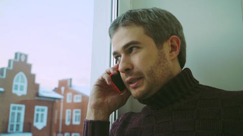 Handsome man in sweater speaking on his phone by the window to townhouses Footage