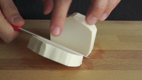 Man cutting off a piece of white soft feta cheese Footage