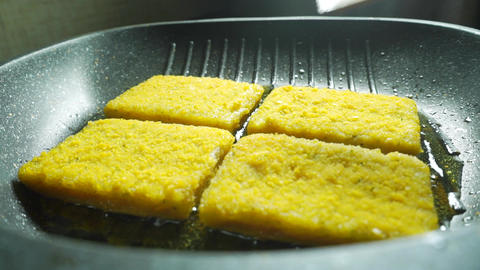 Turning over frying crumbed fish fillets with spatulas, close up video Footage