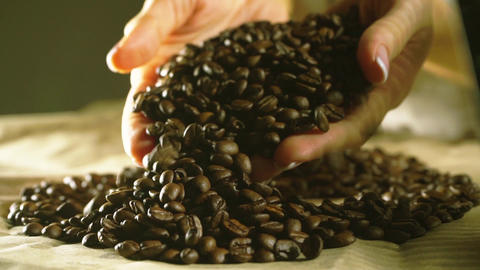 Young woman hands with beautiful nail polish draw some roasted coffee beans GIF