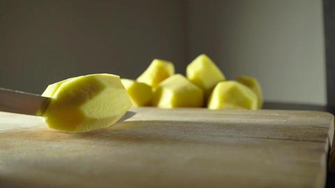 Splitting whole peeled potato with a knife Footage