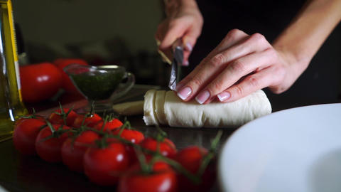 Cutting mozzarella cheese for Caprese salad. Part of the set Footage