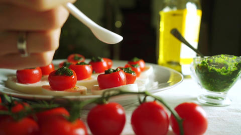 Adding balsamic vinegar to cheese and tomato salad (Caprese). Part of the set Footage