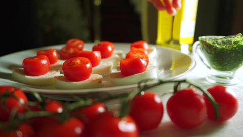 Adding pesto sauce to mozzarella and tomato salad (Caprese). Part of the set Footage