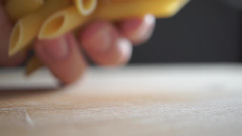 Pouring a handful of penne pasta on wooden cutting board, slow motion video Footage
