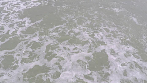 Foamy sea surface and sandy beach fly by video Footage