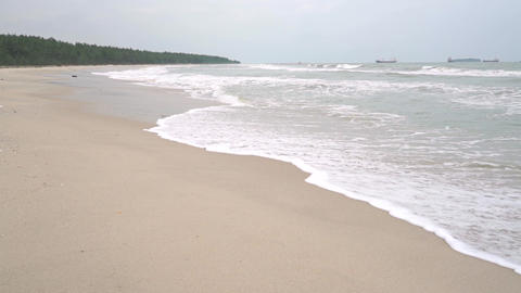 Surf and distant ships. Slow motion video shot on cloudy day Footage