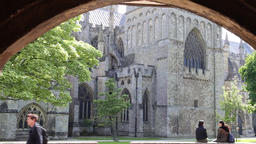 Asian tourists sitting on wall in Cathedral Close Exeter Cathedral Exeter Devon Footage
