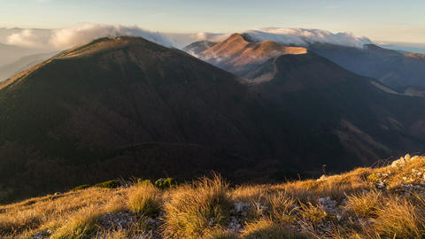 Morning sunlight in mountains with clouds flying over ridge time lapse in autumn Footage