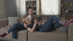 Lesbian couple is resting on the couch, laughing and watching funny movie on Footage