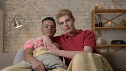 Two gay guys are sitting on the couch and watching TV, an African guy wants to Footage