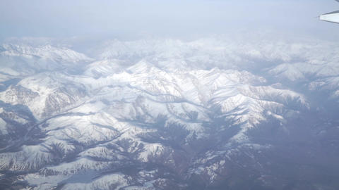 View from airliner porthole with snowy mountains Footage