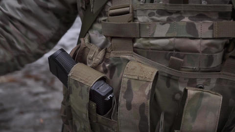 Soldier puts assault rifle ammo into pockets of his ammo vest Footage