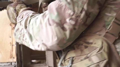 Soldier armed with an assault rifle guarding room near the broken window Footage
