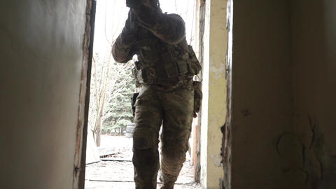 Two unrecognizable armed soldiers creep into hostile ruined building Footage